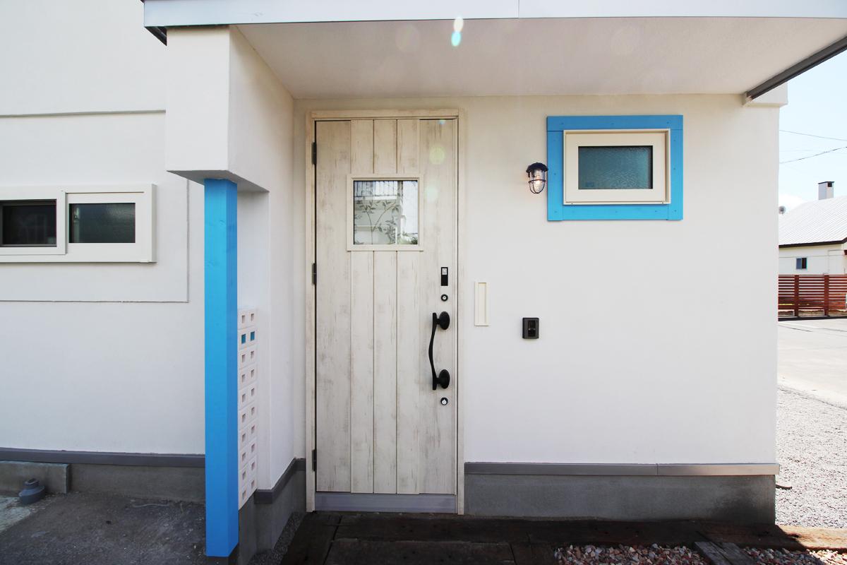 白い壁と水色のライン 北欧テイストの玄関ドア